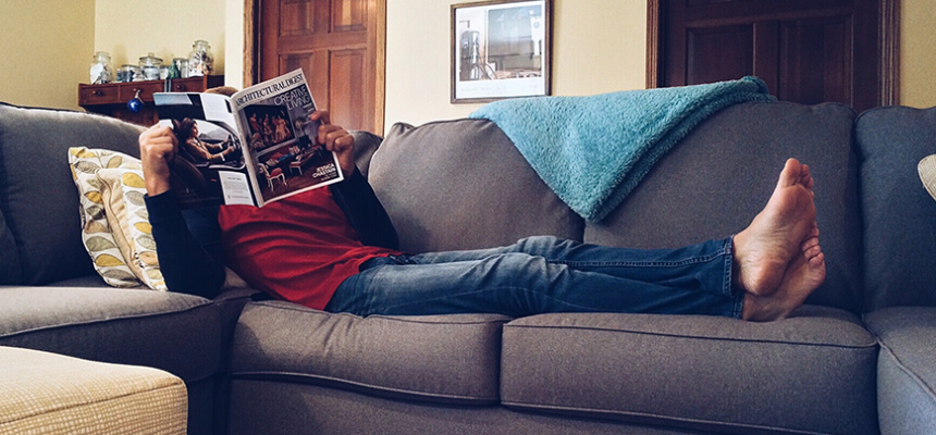 person reading magazine on couch